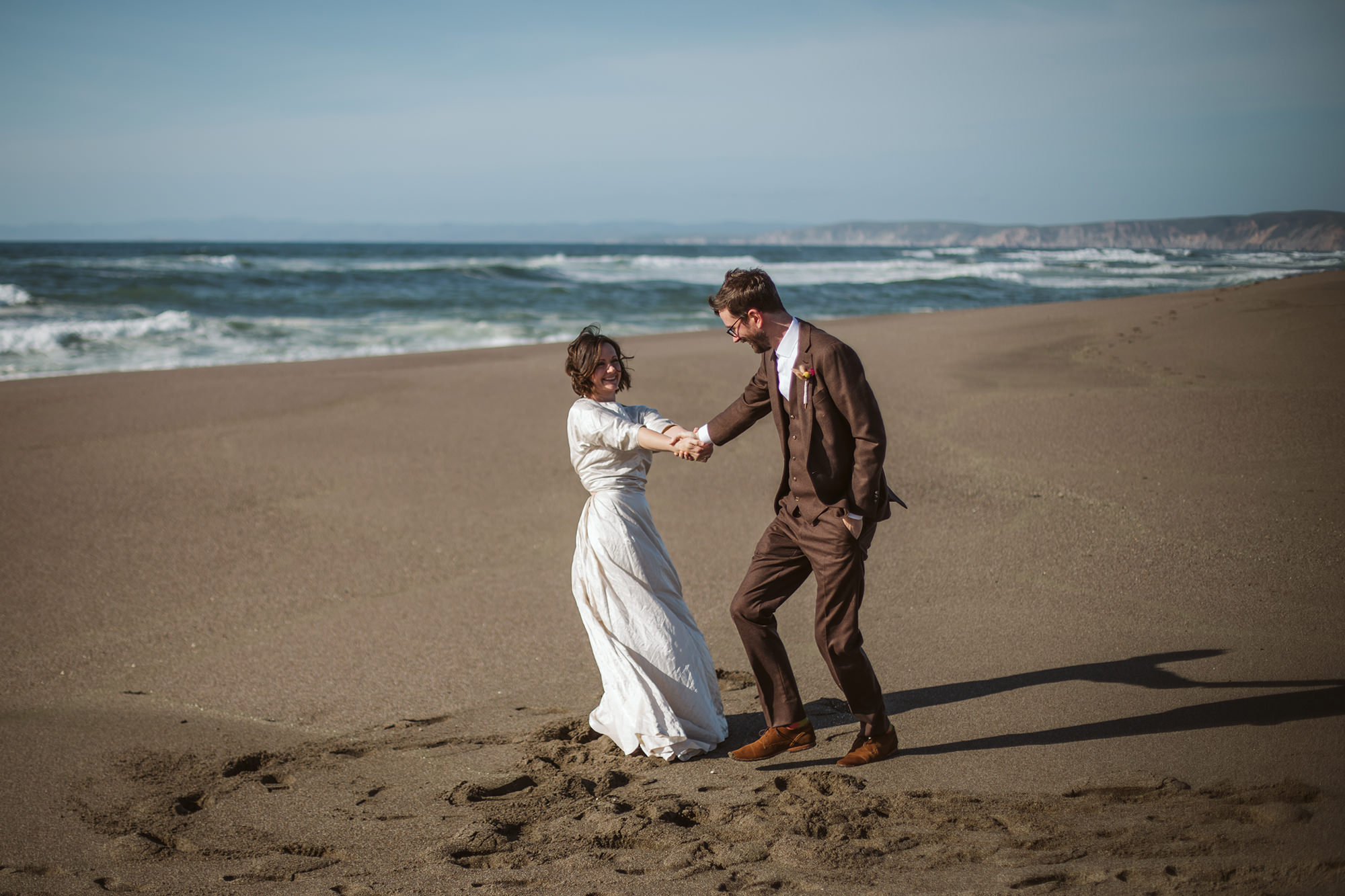 Bride and groom playing on the beach in Point Reyes elopement.