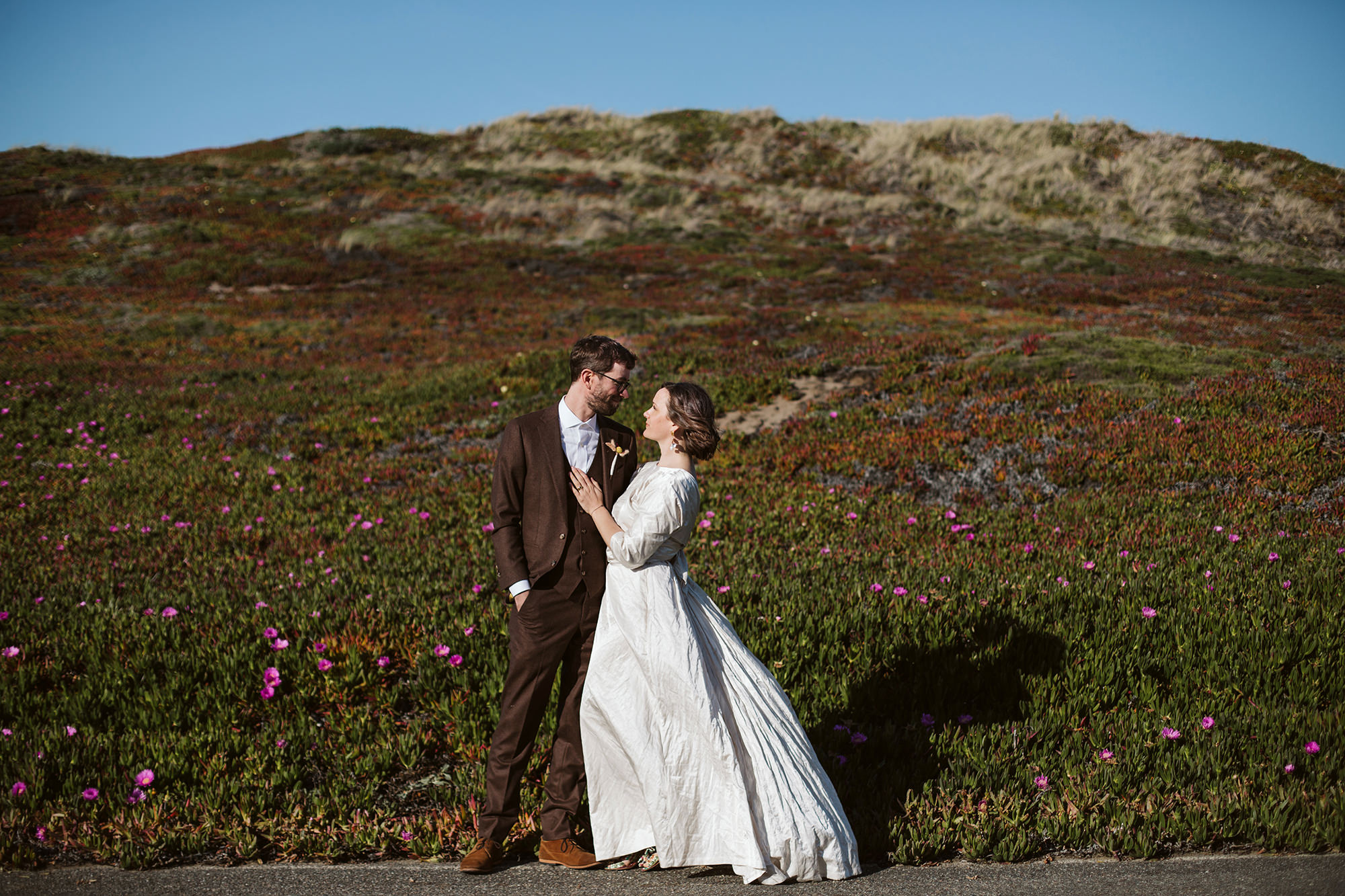 Bride looks into eyes of groom in front of field of succulents at sunset for Point Reyes Elopement.