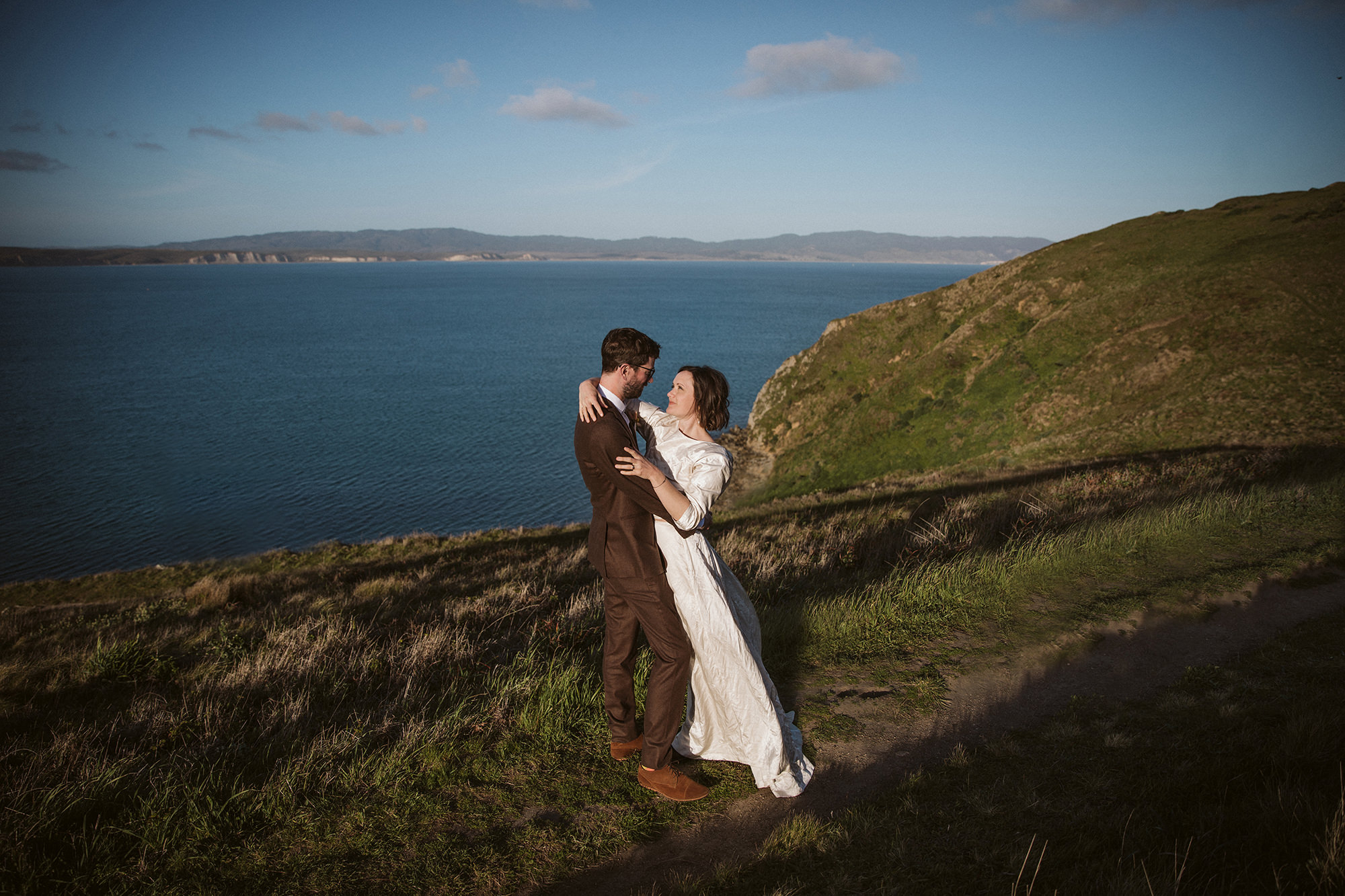 Bride and groom embrace at Chimney Rock for Point Reyes Elopement.