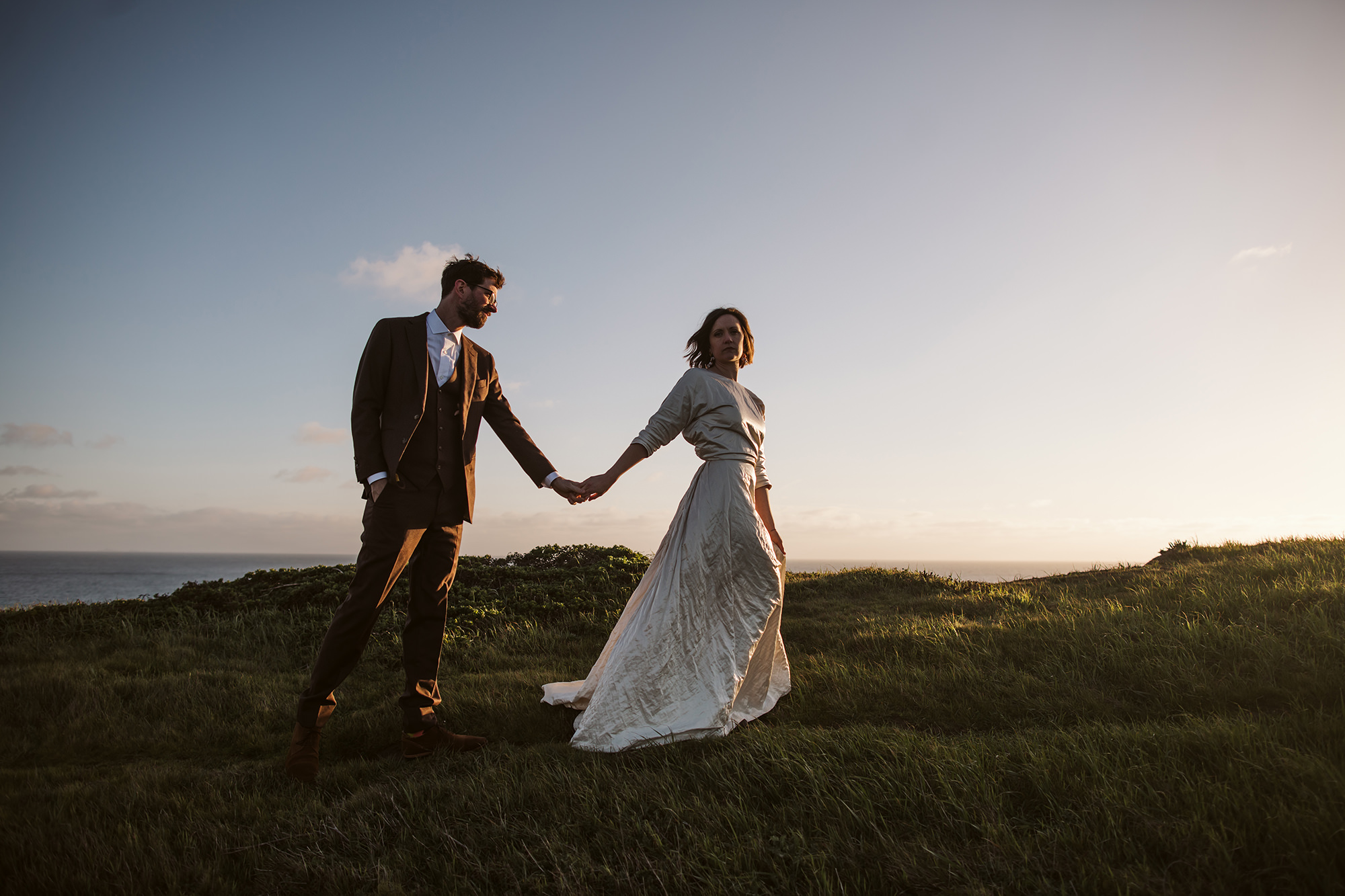 Bride and groom walking into the sunset during their Point Reyes elopement.