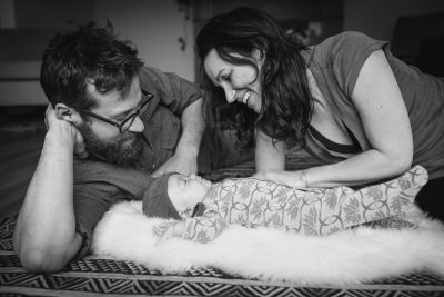 Becca Henry Photography - Oakland Newborn Photography - BW image of parents looking over baby