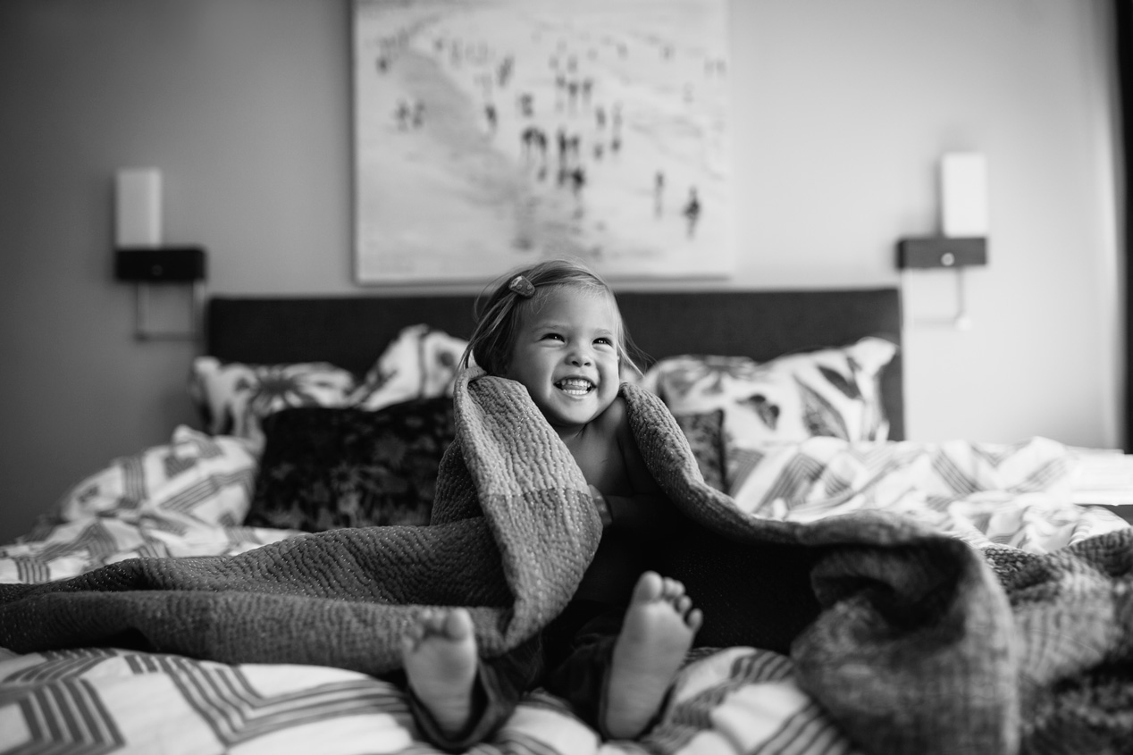 Becca Henry Photography- little girl wrapped up in blankets in parents bed - Family Photography