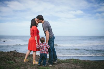 Becca Henry Photography - Oakland Maternity photography- Mom, dad, and 2 year holding hands looking at waves at Pacifica Beach, California.