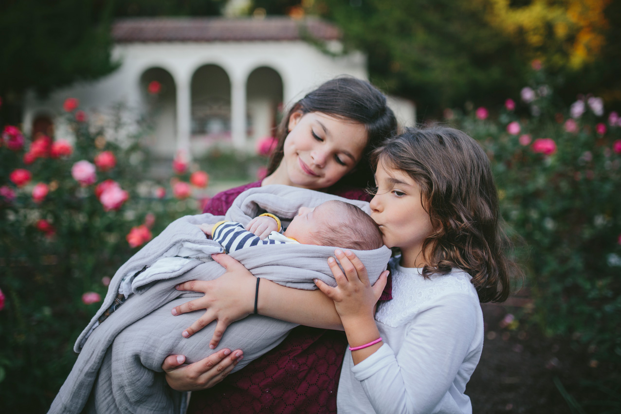 Becca Henry Family Portraits- sisters holding newborn baby brother in Morcom Rose Garden in Oakland
